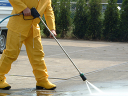 Man in yellow waterproofs pressure washing slabs